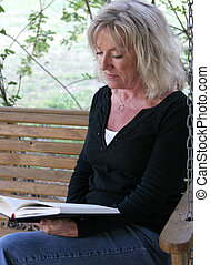 Reading For Pleasure - A beautiful mature woman relaxing and...