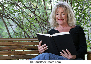 Enjoying A Book - A beautiful woman enjoying a good book on...