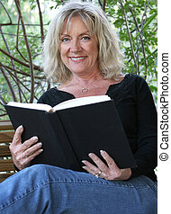 Enjoying A Good Book - A beautiful mature woman relaxing and...