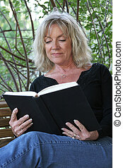 Relaxing With a Book - A beautiful mature woman relaxing and...