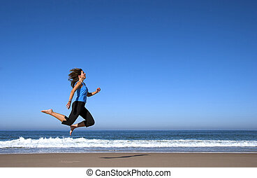 Jumping on the beach - Young active woman alone in the beach...