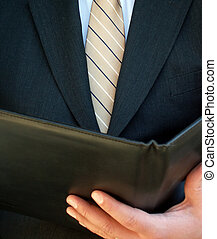 businessman reading from a leather notebook