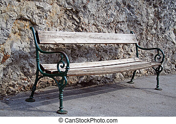 Old bench against rock - Old bench leaning against rock at...