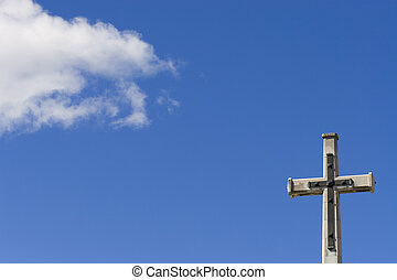 Heaven and Earth - A crucifix shot against a blue sky with a...