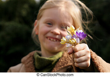 Spring girl - Little girl holding out a bunch of crocuses
