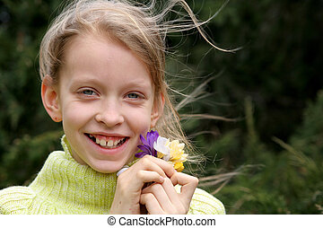 Spring mood  - Young, smiling girl with a bunch of crocuses