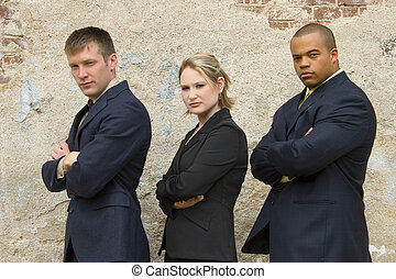Business Team - Three business team members outside in suits...