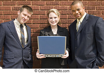 Business Team Laptop - Young business team standing against...