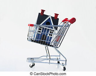 Shopping for a home - Miniature house in a shopping cart...