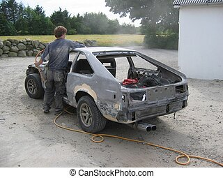 Working on car - Person blowing a car clean from dust