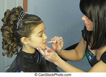 Getting pretty - A young girl gets lip gloss applied by a...