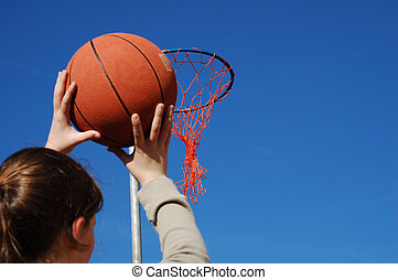Shooting Basketball - Young girl taking aim with a...