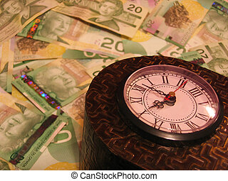 Time is Money - Clock amongst twenty dollar Canadian bills;...