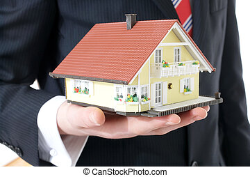 house - Businessman showing a model house
