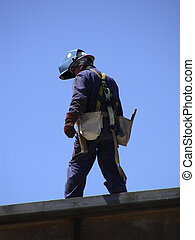 Balancing Act - Welder walking along a steel beam at the top...