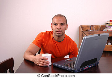 Coffee Break - A man works at his computer and drinks coffee