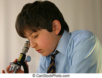 Schoolboy science - Schoolboy in uniform studies a specimen...