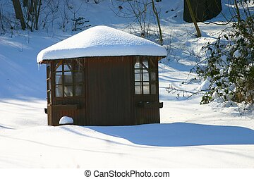 Snow house - A little garden house in deep snow with sun and...