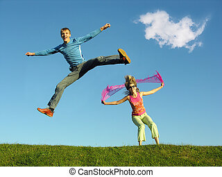couple jump under cloud