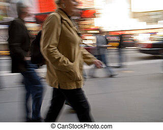 Go Go Go - A motion blur of a woman and others walking down...