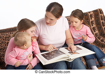 storytelling - mother reads from a book to her kids