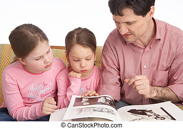 family life - father reads from a book to her kids