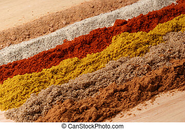 Lines of different spices - from front to back: cinnamon,...