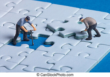 working - plastic workers fixing a puzzle