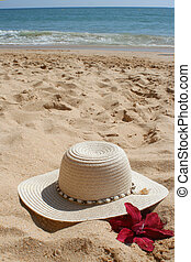 beach hat and flower in the sand