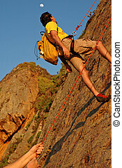Belaying a Partner - Climbers belaying off a cliff at sunset...