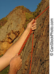 Hands Belaying - A climber belays another climber at sunset