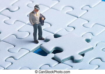 resolution - plastic figure standing in front of a puzzle...