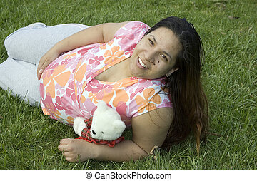 Young Woman - Young woman laying down on grass with a teddy...