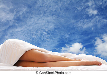 Bed Legs - Woman in bed with blue sky showing through the...