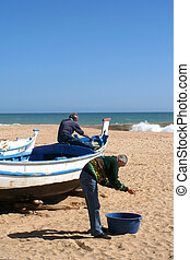fishermen work on the boats at Fishermen\\\'s beach in...