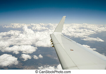 Flying into the Blue Horizon - Photo taken of plane wing,...