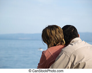 couple hugging, sea in the background