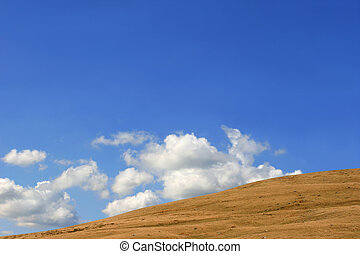 Barren Hillside - Altocumulus clouds in a blue sky above a...