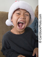 Happy boy in santa hat with mouth wide open showing inside...