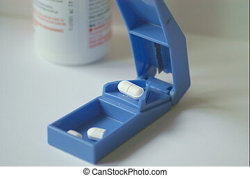 pill chopper - chopping your pill in half with a small blue...