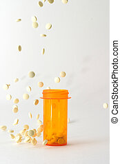 Pills falling into and around medicine bottle - medicine...