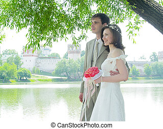 Wedding couple near the water and monastery