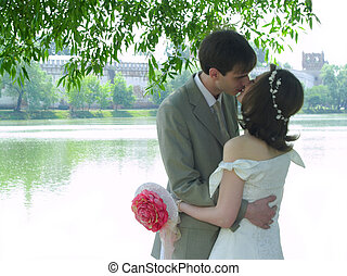 Kissing couple near water and monastery