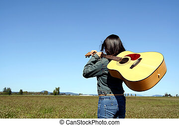 Woman guitar player - A woman holding a guitar looking at an...
