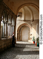 ancient building - woman stands among the arches of an...