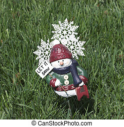 Spring Snow - let it snow figure on green grass depicting...