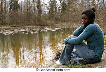 Contemplative - A pretty teenage girl sitting next to a pond...