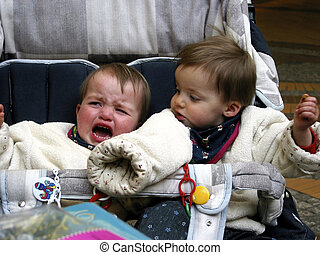 crying twins in the baby carriage - twins in the baby...