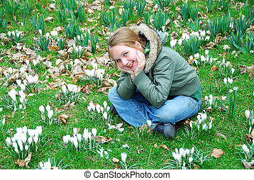 Girl in crocus field - Young girl sitting among blooming...