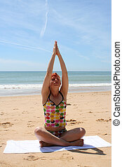 beach yoga 6 - woman does yoga and meditation on beach